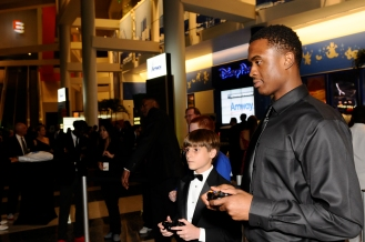 Orlando Magic player Doron Lamb with a young fan playing video games at the Orlando Magic Youth Foundation's (OMYF) 23rd Annual Black Tie and Tennies Charity Gala on March 23 at Amway Center. The OMYF Gala raised more than $500k for the Central Florida community, with matching funds at .50 on the dollar provided by the McCormick Foundation. Photo taken by Gary Bassing.