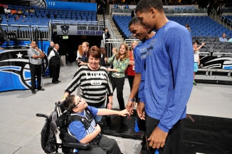 "Orlando Magic's Kyle O'Quinn visits with ten-year-old Caleb Dominguez prior to the Magic's Oct. 25 matchup against the New Orleans Pelicans. Dominguez was named the team's first ""Magic Maker"" and brought to the game for a VIP experience.  Photo taken by Gary Bassing."