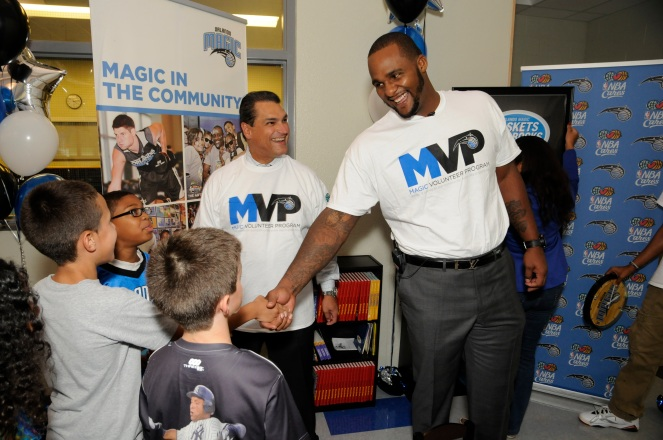 CEO Alex Martins and Magic player Glen Davis show youth at the Goldenrod Park Recreation Center their new reading corner as part of the Magic's 25 reading corners built in one day. Magic staff members through the Magic Volunteer Program (MVP) and Florida Blue employees assisted in the building of the 25 corners. Photo taken by Gary Bassing.