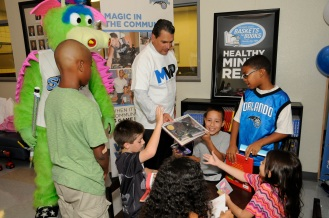 Magic CEO Alex Martins with youth at the Magic's unveiling of one of the 25 reading corners that were built in one day on October 10. Magic staff members through the Magic Volunteer Program (MVP) and Florida Blue employees assisted in the building of the 25 corners. Photo taken by Gary Bassing.