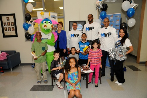 left to right: Early Learning Coalition of Orange County CEO Karen Willis, Magic CEO Alex Martins, Magic player Glen Davis, Florida Blue Market President Central Florida Region Tony Jenkins, Magic Dancer Elyse along with youth from the Goldenrod Park Orange County-Orlando Magic Recreation Center. The Magic celebrate the unveiling of one of the 25 reading corners that were built in one day on October 10. Magic staff members through the Magic Volunteer Program (MVP) and Florida Blue employees assisted in the building of the 25 corners. Photo taken by Gary Bassing.
