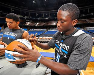 Orlando Magic players Tobias Harris (left) and Victor Oladipo (right) sign approximately 300 basketballs during the internal team autograph session on Nov. 15. All autographed items will be distributed back into the Central Florida community. Photo taken by Fernando Medina.