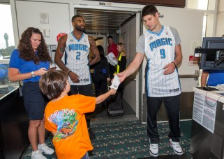 """Orlando Magic players Nikola Vucevic (no. 9) and Kyle O'Quinn (no. 2) """"trade places"""" with Southwest Airlines all-star employees on Nov. 19. The players took boarding passes along with signing autographs and visiting with passengers as part of the event. Photos taken by Fernando Medina."""
