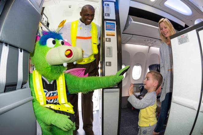 Orlando Magic mascot STUFF and Magic Community Ambassador Bo Outlaw help marshall in a Southwest Airlines aircraft as part of the trading places event with Southwest Airlines all-star employees on Nov. 19. The Magic's mascot and Outlaw joined Magic players in signing autographs, visiting with passengers and collecting boarding passes. Photo taken by Gary Bassing.