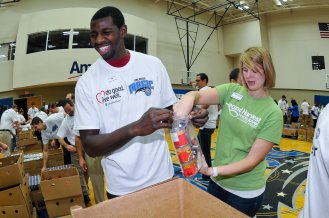 Magic player Andrew Nicholson works with Second Harvest's Jennifer Landress to assemble 13,500 food packs for youth. Nicholson and Landress joined 300+ Magic staffers and UHC employees to assemble the food packs. The packs will be donated to the Second Harvest Food Bank of Central Florida as part of their Hi-Five Kids Packs Program. Photo taken by Fernando Medina.