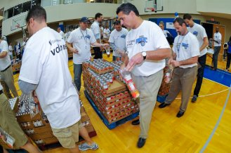 Magic CEO Alex Martins (left) and Magic player Maurice Harkless (right) joined 300+ Magic staffers and UnitedHealthcare employees to assemble 13,500 food packs as part of the Magic and UHC's efforts to fight childhood hunger in Central Florida. The packs will be donated to the Second Harvest Food Bank of Central Florida as part of their Hi-Five Kids Packs Program. Photo taken by Fernando Medina.
