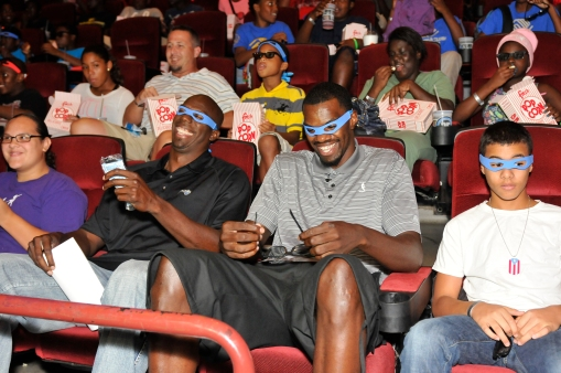 Magic player Dewayne Dedmon (right) and Magic Community Ambassador Bo Outlaw (left) host local youth to a movie, popcorn, drinks and a special Magic goody bag. In the Magic's continuing efforts to get kids ready for school, the Magic along with Dedmon hosted youth at a private screening of Teenage Mutant Ninja Turtles on August 7. Photo taken by Gary Bassing.