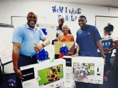 the Orlando Magic and Magic guard Victor Oladipo surprised youth and representatives from the New Image Youth Center in Parramore with all new equipment including big screen TVs, video games and computers after most of these items were stolen earlier in the week. Pictured left to right: Magic Community Ambassador Nick Anderson and Bo Outlaw, City Commissioner Regina Hill, Magic guard Victor Oladipo with TVs before surprising the kids at the center. Photo taken by Gary Bassing.
