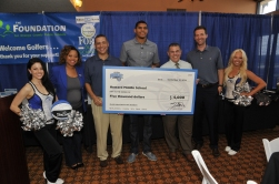 left to right: Magic Dancer Jamie; Magic Assistant Director of Community Relations Latria Leak; Magic VP/Asst. GM Scott Perry; Magic Forward Tobias Harris, Howard Middle School Principal Paul Maldonado; Magic GM Rob Hennigan; Magic Dancer Nicole. On Friday, September 12, Tobias Harris presented Howard Middle School a check for $5,000 as part of the $50k he distributed to Orange County Public Schools as a result of the Rich and Helen DeVos Community Enrichment Award. Photo taken by Gary Bassing.