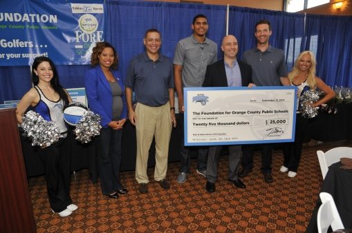 Pictured left to right: Magic Dancer Jamie; Magic Assistant Director of Community Relations Latria Leak; Magic VP/Asst. GM Scott Perry; Magic Forward Tobias Harris, Howard Middle School Principal Paul Maldonado; Magic GM Rob Hennigan; Magic Dancer Nicole. On Friday, September 12, Tobias Harris presented Howard Middle School a check for $5,000 as part of the $50k he distributed to Orange County Public Schools as a result of the Rich and Helen DeVos Community Enrichment Award. Photo taken by Gary Bassing.