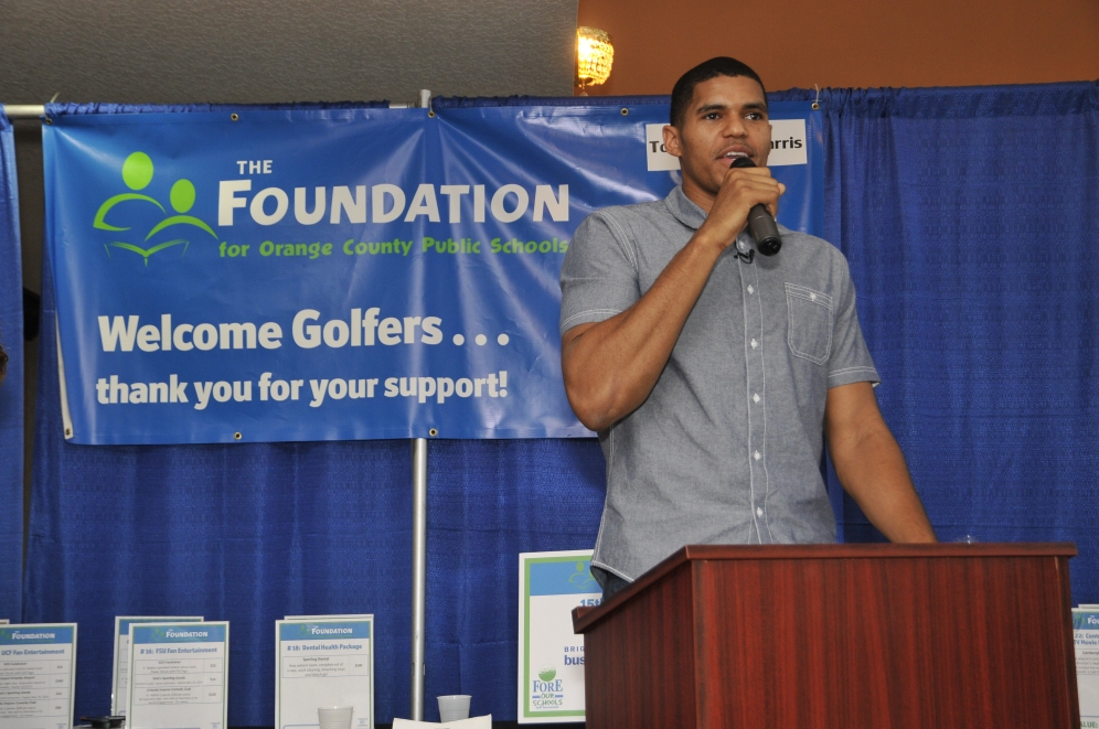 """On Friday, September 12, Magic forward Tobias Harris speaks to the crowd at Orange County Public Schools """"Fore Our Schools Golf Tournament"""" prior to presenting checks totaling $50,000 to two Orange County schools and the Foundation for Orange County Public Schools for their educational programs. The donation was made possible through Harris winning the 2013-14 Rich and Helen DeVos Community Enrichment Award for his off-the-court efforts. Photo taken by Gary Bassing."""