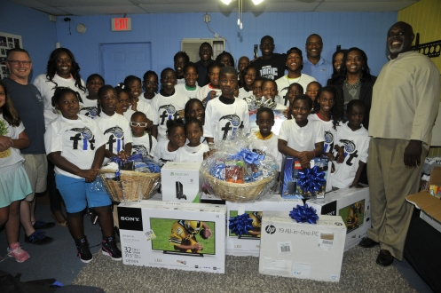 the Orlando Magic and Magic guard Victor Oladipo surprised youth and representatives from the New Image Youth Center (NIYC) in Parramore with all new equipment including big screen TVs, video games and computers after most of these items were stolen earlier in the week. Pictured: Victor Oladipo (center), City Commissioner Regina Hill (right), New Image Youth Center Founder/Executive Director Shanta Barton-Stubbs (far left), Magic Community Ambassadors Nick Anderson (back left) and Bo Outlaw (back right) and NIYC youth. Photo taken by Gary Bassing.