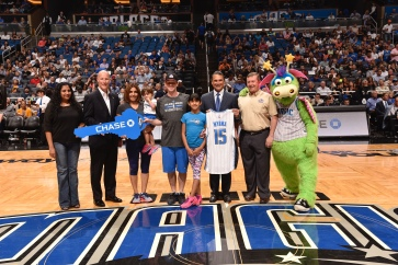 all photos taken by Gary Bassing, Orlando Magic): As part of Fan Appreciation Weekend, the Magic teamed up with Chase and Building Homes for Heroes for a special home award presentation along with others surprises for the Wyrwa family including Disney Park Hopper passes, a two-night Marriott Vacation Club stay, a 40, inch television, $1,500 for home furnishings and new bicycles for the girls. Magic CEO Alex Martins, Senior Vice President and Retail Banking Market Manager at JP Morgan Chase Greg Fahey, Building Homes for Heroes representative, and the Wyrwa family (Alan, wife Erika and daughters Camila and Ariel) joined at center court at the April 11 Magic vs. Knicks game for the special presentation.